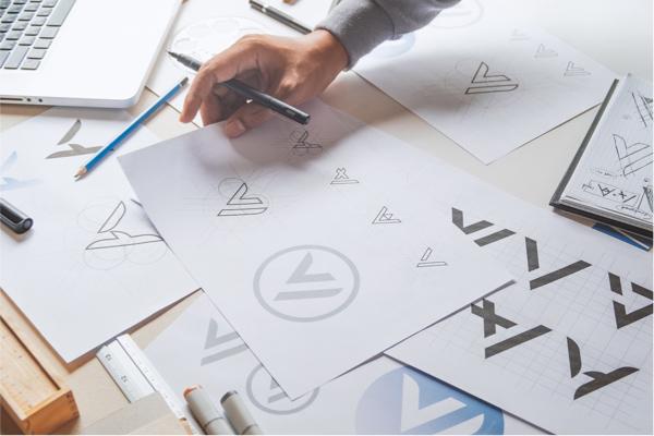 hombre diseñando logo en hojas de papel