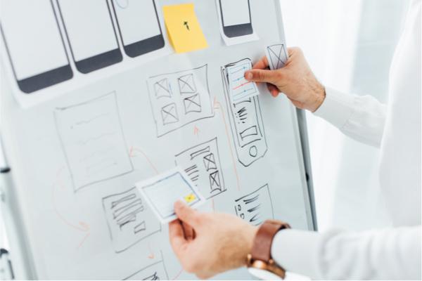 persona diseñando aplicativo movil sobre tablero